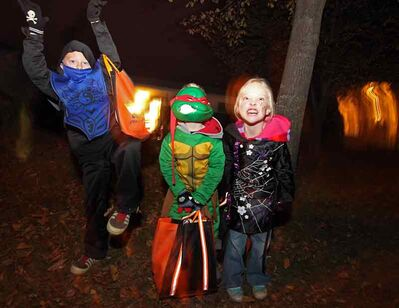 Trick-or-treaters James Frendo, Jonah Frendo and Madison Frendo show off their costumes while out collecting candy on Christie Bay in Brandon on Halloween.