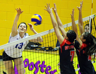 Brandon Bobcats left side Jaryn Ruether hammers the ball past Erika Buchanan (middle) and Ellina Domnidou of the Winnipeg Wesmen during women's volleyball action Friday night at Brandon University.