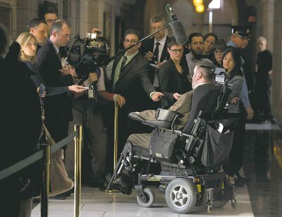 Steven Fletcher speaks with the media as he leaves caucus on Parliament Hill in Ottawa on Wednesday.