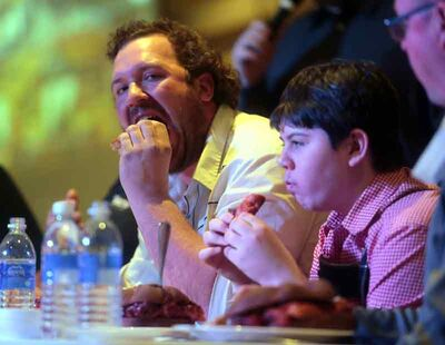 Jae Jae Bartel takes a big bite out of his two-and-half pound Leberkase sandwich during Saturday's Leberkase Eating Contest at the German pavilion. Four of the five competitors had to bow out, including Bartel and 13-year-old Max Halleman, during the competition.