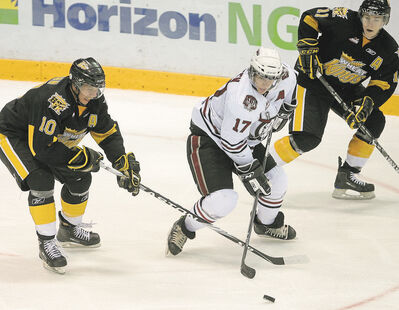 Red Deer Rebels forward Nathan Green splits between Brandon Wheat Kings Brayden Schenn, left, and Matt Calvert, right, during a game on Oct. 2, 2009. Green had a goal and two assists aginst his former squad in a Red Deer victory.