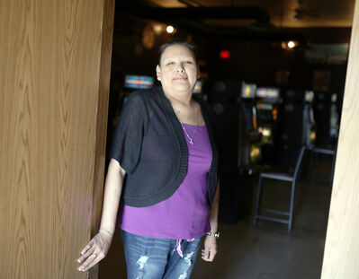 Sioux Valley Dakota Nation member Candace Tacan smiles from the back doorway of her workplace. Her uninsured home was heavily damaged by the tornado that struck the community last summer, but she has received a new garage, porch and other repairs, below.