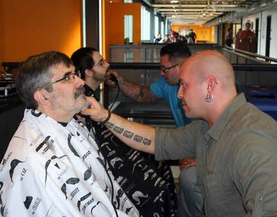 Kim Martin gets his moustache shaved off for the first time since 1977, by Quentin Derhak of Bladeworx Barber/Salon at the Assiniboine Community College Movember campaign kickoff. In the second chair, Tim Blampied gets shaved by Jesse Spence.