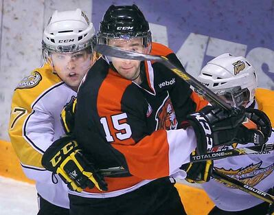 Brandon Wheat Kings left-winger John Quenneville (left) and Medicine Hat Tigers centre Elgin Pearce tangle behind the visitors' net during Western Hockey League action on Wednesday evening at Westman Place.