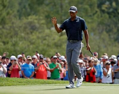 Tiger Woods reacts after making a birdie on first hole during the first round of the PGA Championship golf tournament at Bellerive Country Club, Thursday, Aug. 9, 2018, in St. Louis. (AP Photo/Jeff Roberson)