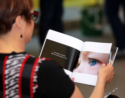 A visitor studies one of the exhibit photos, which were taken by people who have experienced suicidal thoughts, attempted suicide, or survived someone who committed suicide.