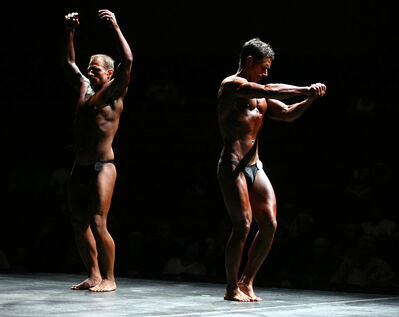 Ryan Jacobson (right) in the novice men's category flexes onstage during the International Drug Free Athletics Prairie Classic bodybuilding competition.