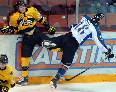 Brandon's Nick Walters and Kootenay's Jordyn Boyd collide along the boards Friday at Westman Place.