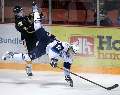 Wheat Kings captain Ryan Pulock rocks Blades forward Lukas Sutter with a big hit in the first period Tuesday.