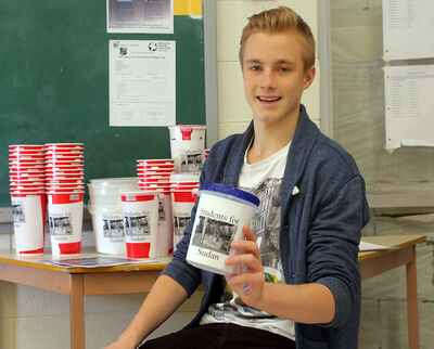 Student council president Alec Chambers shows some of the collection cups that Vincent Massey high school students are using raise funds for refugee camps in South Sudan and a school in Ecuador.