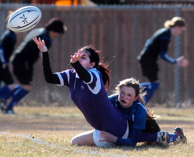 Vincent Massey's Kelli Abad tosses the ball to a teammate as she is tackled by Kaylee Butterfield of Souris during Westman high school rugby action on Tuesday afternoon.