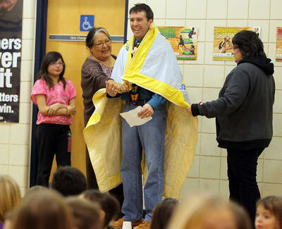 Principal Shawn Lehman is draped with a traditional aboriginal star blanket by Viola Fleury, right, and Amie Martin at an assembly at J.R. Reid School on Friday. Fleury's daughter Jayna, left, helped organize the donation of the blanket to the school as a cultural initiative.