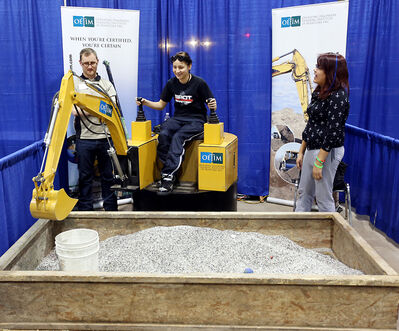 In this March 2013 photo, Fleming High School student Annie Cloud operates a scaled-down digger as Billy Elias with Operating Engineers Training Institute of Manitoba and friend Leigha Cloud look on during the 28th annual Brandon Career Symposium at the Keystone Centre.