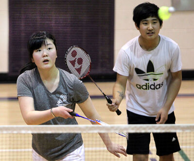Mona Zhang hits a shot as partner Carl Ding looks on during the mixed doubles event of the city high school badminton championships at Vincent Massey on Wednesday.