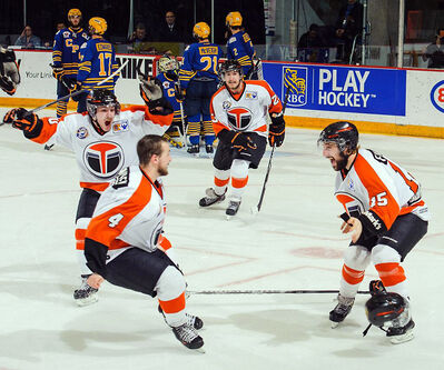 Russell's Derek Falloon (right) celebrates his overtime winner with his Yorkton Terriers teammates Sunday.