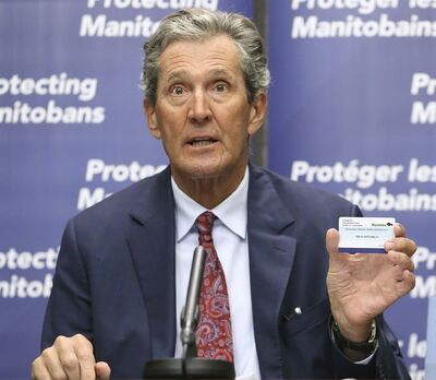Premier Brian Pallister holds a vaccination card during a press briefing on vaccine measures at the Manitoba Legislative Building in Winnipeg on Tuesday. The card would allow Manitobans to skip the quarantine process upon returning from domestic travel within Canada. (Winnipeg Free Press)</p></p>