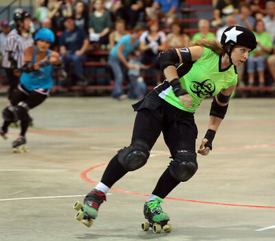 Gang Green's Kristin Shukin, a.k.a. Holey Mow-zes!, speeds her way around the track during the roller derby match.