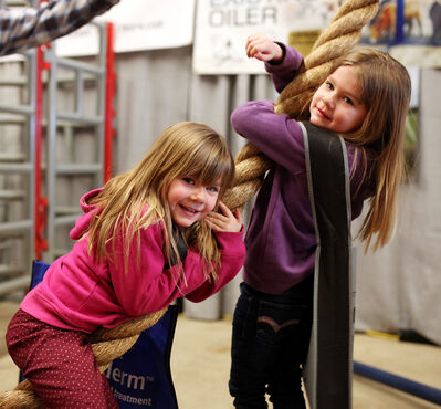 Four-year-old twins Grace and Ella Dalton play on a cattle oiler as Manitoba Ag Days kicked off at the Keystone Centre on Tuesday.