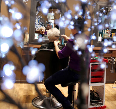 Nearly New Shop volunteer Amy Knight is framed by lights as she has her hair cut and styled by Straight Up Salon hairstylist Zack Savage during a morning of pampering on Wednesday.