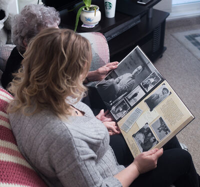 Jodi Douglas, right, and her grandmother Winelda Curtis look at a scrap book featuring news clippings and photos of Ernie Curtis Saturday. (Chelsea Kemp/The Brandon Sun)