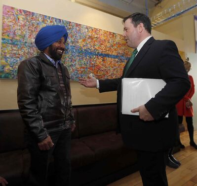 Minister of Employment and Social Development and Multiculturalism, Jason Kenney speaks with Satnam Dolla, a newly arrived immigrant from India while touring Immigrant Centre Manitoba Wednesday.