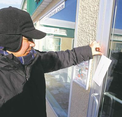 BORIS MINKEVICH / WINNIPEG FREE PRESS Niigaanwewidam James Sinclair tapes letter on the front door of the Morris Mirror office Tuesday.