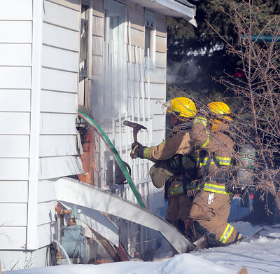 Firefighters work to control a fire in the walls of a home on the 600-block of 12th Street shortly after 5 p.m. on Wednesday.