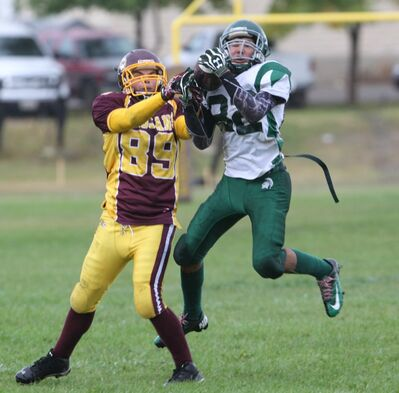 Neelin Spartans standout Quinton Hunter (right) intercepts a pass —one of his nine last season — during a Winnipeg High School Football League clash with the Portage Trojans on Sept. 19.