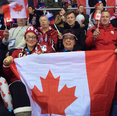 Jen Zimmer (left) and her mother Heidi Howarth sit in a sea of Canada flags during the gold medal match between Canada and Sweden at the Bolshoy Ice Dome in Sochi on Sunday.