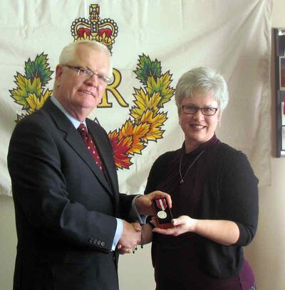 Brandon-Souris Conservative MP Merv Tweed presents a Queen's Diamond Jubilee Medal to Karen Morrow-Penner on Tuesday.