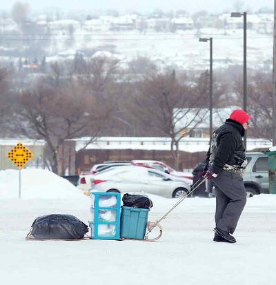 Pulling his belongings on a toboggan, a pedestrian makes his way downtown along Rosser Avenue in the frigid temperatures on Monday.