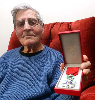 Les Downing, seen with his Second World War medals at his home in Virden in 2015, is set to receive a COVID-19 vaccine Wednesday.