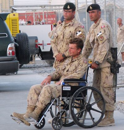 Pte. Glen Kirkland, in a wheelchair, one of five soldiers injured in a direct fire explosion, attends a ramp ceremony for fallen comrades Cpl. Andrew Grenon, Cpl. Mike Seggie and Pte. Chad Horn, in Kandahar, Afghanistan, in 2008.