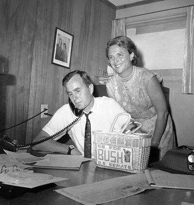 FILE - In this June 6, 1964, file photo George H.W. Bush, candidate for the Republican nomination for the U.S. Senate, gets returns by phone at his headquarters in Houston, as his wife Barbara, smiles at the news. Bush died at the age of 94 on Friday, Nov. 30, 2018, about eight months after the death of his wife, Barbara Bush. (AP Photo/Ed Kolenovsky, File)