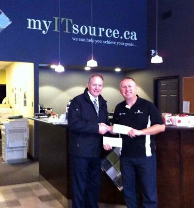 Frank Arndt, right, owner of myITsource.ca & Corral Communications, hands Chuck Elliott, fundraising campaign chair for the United Way, a cheque for $2,500 on behalf of the staff at Corral Communications and myITsource.ca