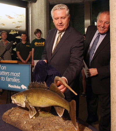 MLAs Gord Mackintosh (left) and Ron Lemieux introduce the walleye as Manitoba's official fish Thursday.