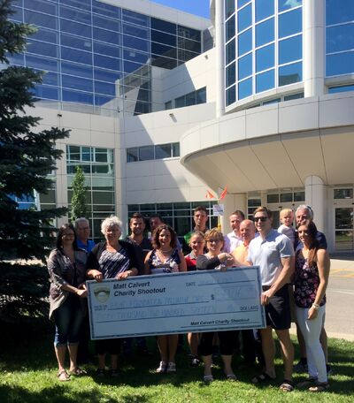 Matt Calvert shakes the hand of Linda Noto, chair of the Brandon Regional Health Centre Foundation, as he presents $50,216.08 to the foundation to upgrade the Palliative Care Unit. Family, friends and supporters are also pictured.