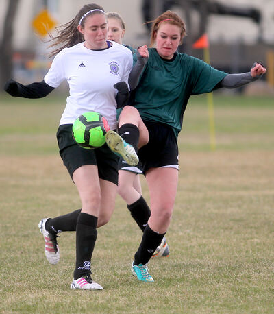 Vincent Massey's Tara Vancauwenberghe (left) and Neelin's Alana Levandoski battle for a loose ball during Tuesday's high school girls soccer match at Vincent Massey.