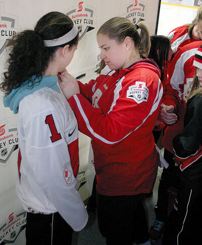 Cherie Piper autographs a jersey for a young local female hockey player on Monday at Westman Place.