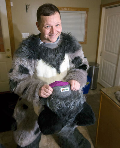 Justin Zinger, a.k.a. Toasty the Avocado Snep snow leopard, puts on his fur suit on Nov. 14.