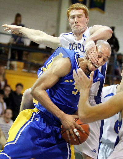 Isaiah James of the Brandon Bobcats is fouled by Mike Berg of the Victoria Vikes in CIS men's basketball action Saturday night at the BU gym.