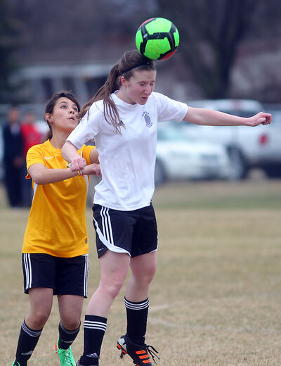 Vincent Massey Vikings' Anna Lysack heads the ball in front of Crocus Plains' Paula Aguiese during Tuesday's high school soccer match at Vincent Massey.