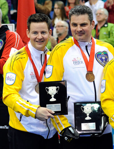 Skip Rob Fowler (left) and third Allan Lyburn celebrate their bronze medals at the 2012 Canadian men's curling championship.