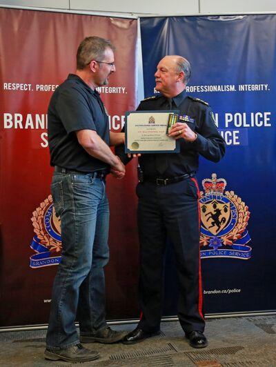 Const. Russ Paterson is congratulated by Brandon Police Service Chief Ian Grant while receiving a Distinguished Service Medal during Tuesday's ceremony. Patterson was recognized for 12 years of service.