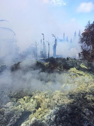 This Tuesday, May 15, 2018 photo provided by the U.S. Geological Survey shows incandescence observed at Fissure 14 around 10:30 a.m. HST at Kilauea Volcano, in Hawaii. Pulsing, gas-rushing sounds could be heard coming from the crack. Yellow sulfur deposits appear on the crack margins. (U.S. Geological Survey/HVO via AP)
