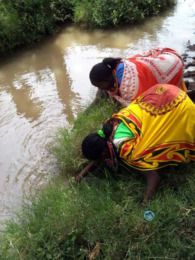 """Two of """"the Mommas"""" gather water that they and the students would carry back to one of Maasai homes."""