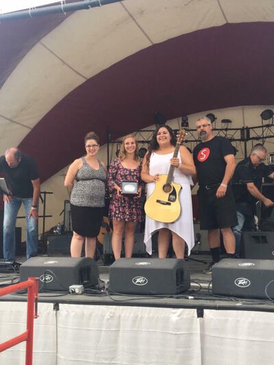 Moore celebrates after winning the competition at the Yorkton Summer Fair on July 8. She is joined on stage by GX94 midday host Tonya Cherry, left, GX94 promotions and marketing director Kayla Jelinski and Garth Malayney with Saddles and Steel.