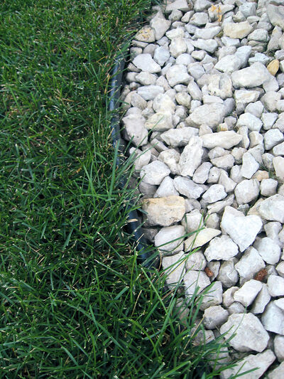 Plastic/vinyl edging products are used to prevent invasion by grass; here it separates crushed limestone mulch from the lawn.