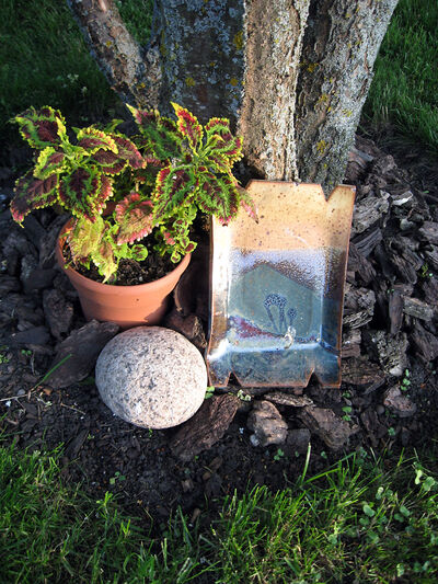 A composition need not be complicated. A stone, a potted plant, and a decorative object combine here to create a tableau, with a tree trunk as a backdrop. Notice that one of the colours in the plaque echoes the colour of the plant's foliage.