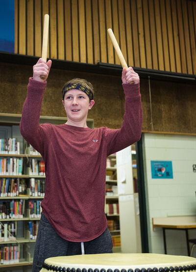 Grade 9 student Evan Black plays a Japanese drum provided by the Winnipeg group Hinode Taiko in the Vincent Massey High School library Thursday. (Chelsea Kemp/The Brandon Sun)